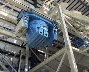 Fig. 7: One of four flying buckets is poised below its mixer discharge gate awaiting the next batch of fresh dry cast mix